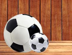 Soccer (football) balls on wooden table Stock Photos