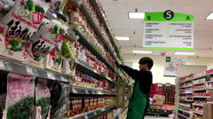 Grocery clerk stocking food in T&T supermarket - stock footage