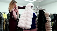 Girl chooses a fur coat faux fur at the store. Stock Footage
