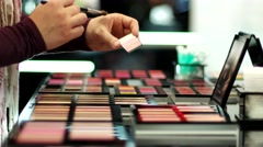 Girl in the shop put a brush makeup for samples to purchase. - stock footage