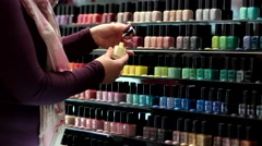 Many rows of multi-colored nail polish to cosmetics store. - stock footage