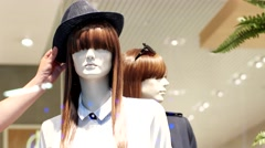Seller straightens his head with a cap on a mannequin in a clothing store. Stock Footage