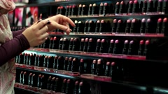 The girl at the store chooses shade of lipstick on the hand trying. - stock footage