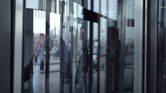People enter into the rotating spinning revolving glass doors. Stock Footage