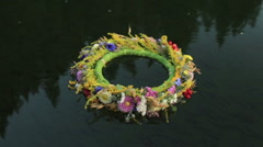 A grass and flower wreath floating on the water. Ethnic decor. Slavic tradition Stock Footage