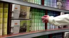Woman taking some palatte color scales inside Home depot store Stock Footage