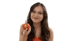 Young woman eating a red tomato indoors against a white background Stock Footage