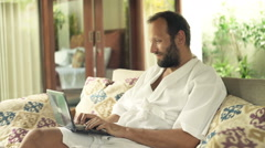 Young man using laptop while sitting on sofa in outdoor villa Stock Footage