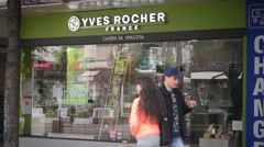 Shopping woman comes out of the store Yves Rocher Stock Footage