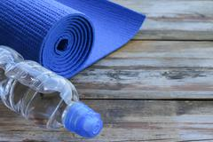 bottle of water and a yoga mat - stock photo