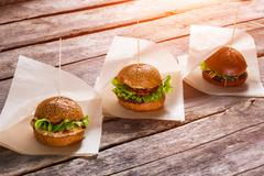 Hamburgers on white wrappers. - stock photo