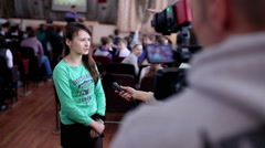 Girl gives an interview in auditorium Stock Footage