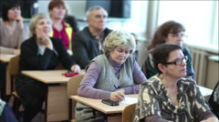 Aged people listen to a lecture sitting in a classroom Stock Footage