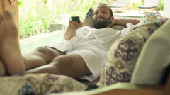 Happy man in bathrobe lying on sofa and watching TV in outdoor villa Stock Footage