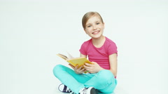 Cute girl 7-8 years hugging book on white background and smiling at camera - stock footage