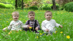Three children on the grass on which the petals are falling from the trees, slow - stock footage