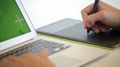 Close up of hands of a young designer using a tablet and a laptop computer Stock Footage