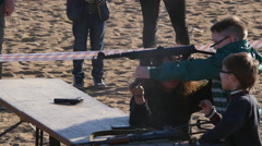 boy shoots a machine gun.Exhibition of weapons - stock footage
