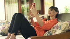 Young, happy woman taking selfie photo with cellphone on sofa in outdoor villa Stock Footage