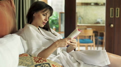 Young woman in bathrobe reading book on bed at home Stock Footage