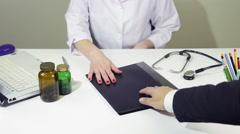 Businessman give bribe, money to female doctor inside folder, envelope Stock Footage