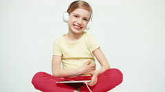 Cute girl 7-8 years old using tablet pc on white background and listening music Stock Footage