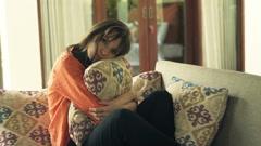 Sad, unhappy woman hugging pillow on sofa in outdoor villa - stock footage