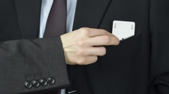 Businesswoman put ace, playing card to businessman pocket, closeup Stock Footage