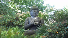 Big sitting Buddha statue in sunny nature environment Stock Footage