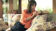 Young, pretty woman using smartwatch on sofa in outdoor villa Stock Footage