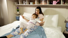 Little girl with mother lying in bed watching cartoon on tv  Stock Footage