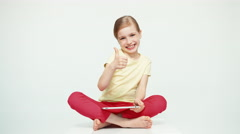 Cute girl 7-8 years old using tablet pc on white background. Thumb up. Ok Stock Footage