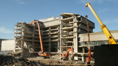 Demolishing a large concrete building with a high reach demolition excavator. Stock Footage