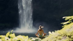 girl meditating in front of waterfall - stock footage