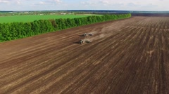 The tractor sows the field on a background of green plantations and clouds. View Stock Footage