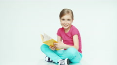 Cute girl 7-8 years reading book and smiling on white background. Thumb up. Ok - stock footage