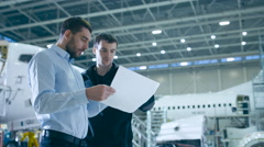 Aircraft Maintenance Worker and Engineer having Conversation. Holding Project. Stock Footage
