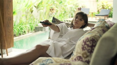 Happy woman in bathrobe lying on sofa and watching TV in outdoor villa Stock Footage