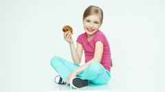 Cute girl child 7-8 years eating muffin and looking at camera and sitting Stock Footage