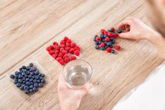 Closeup on man with a glass of water healthy berries on table Stock Photos