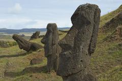 Partially buried Moai statues at the base of volcano Rano Raraku Stock Photos