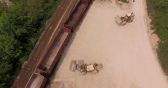 Earthmovers, excavators loaded gravel and stone on train Stock Footage