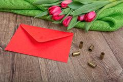 Envelope, tulips and bullets on a wooden background - stock photo