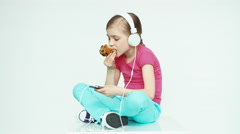 Cute girl child 7-8 years eating muffin and using mobile phone and listening Stock Footage
