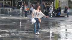 Young woman play with fountain water in new modern district in Milan - stock footage