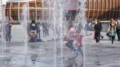 Children play with fountain water at a new modern district in Milan Italy Stock Footage