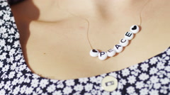 Static shot of beads around a female neck spelling out Peace - stock footage