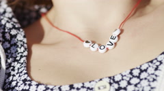 Static shot of beads around a female neck spelling out Love Stock Footage