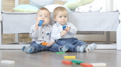 Two lovely baby twins are building houses of  colorful cubes Stock Footage