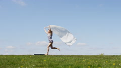 Young female runs along with a silky scarf trailing behind her, in slow motion - stock footage